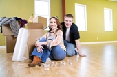 Couple sitting on the floor with boxes